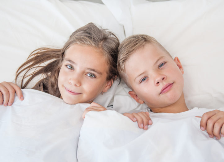 boy and girl lie under a blanket touching their hair.